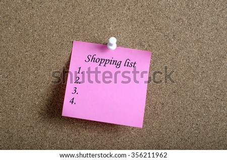 Reminder sticky note on cork board with SHOPPING LIST text - stock photo