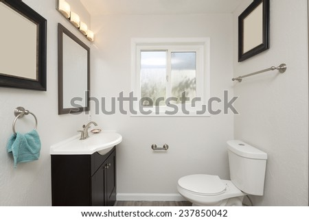 Remodeled bathroom in white with turquoise towel, white sink and window - stock photo