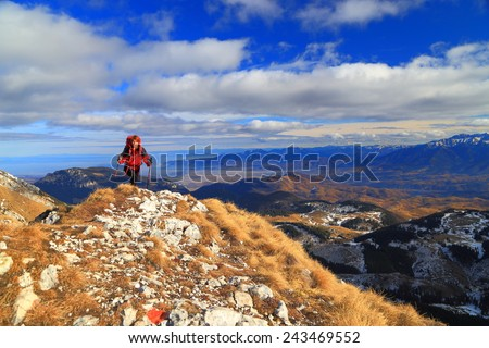 Remote backpacker woman walking on mountain top trail in sunny autumn day - stock photo
