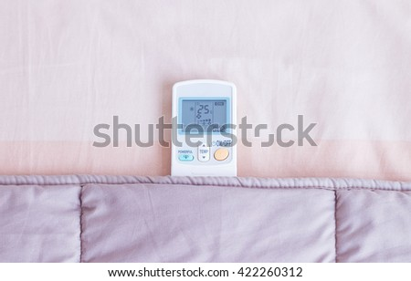 Remote control air-conditioner under blanket in bedroom. - stock photo