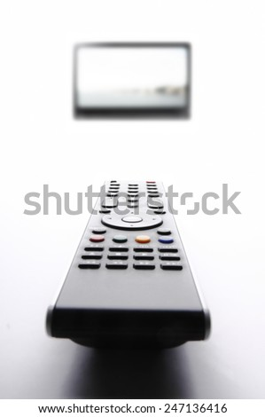 Remote control and TV in the background. - stock photo