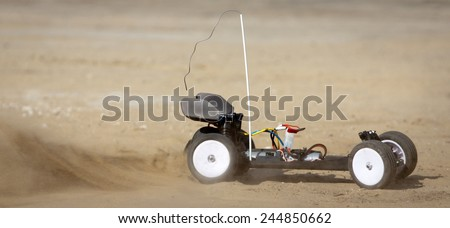 Remote control car running on sand - stock photo