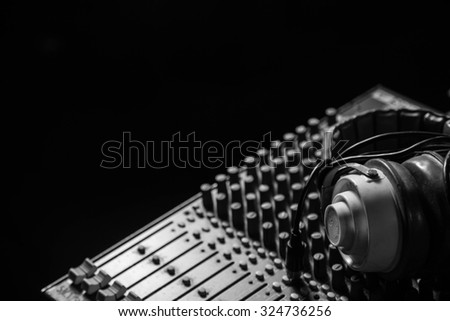 Remote control for audio recording . Mixing console for audio recording with earphone on it. - stock photo
