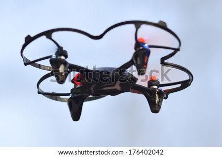 remote controlled quadcopter drone in mid air - stock photo