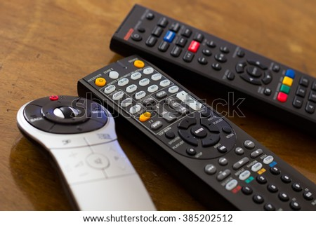 Remote controls on the wooden table - stock photo
