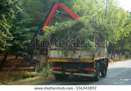 Remote manipulator collecting trees near the road. - stock photo