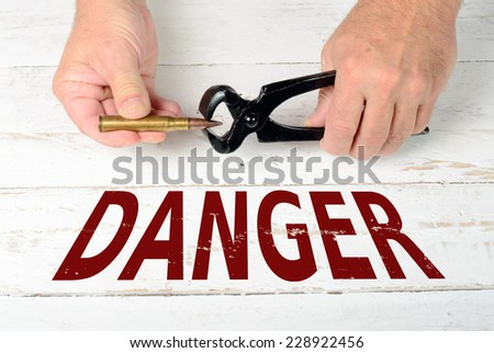 remove a bullet cartridge with pliers is dangerous - stock photo