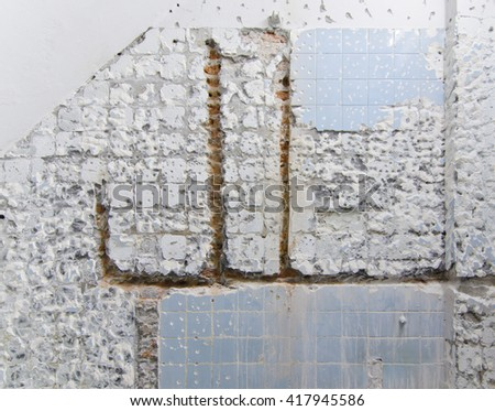 Removing, demolishing old durable wall tiles and pipes in a bathroom for new renovation - stock photo