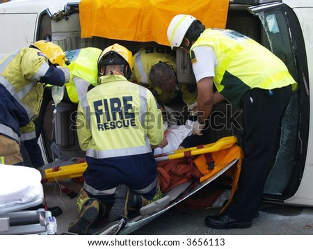 Removing Driver from Wrecked Car - stock photo