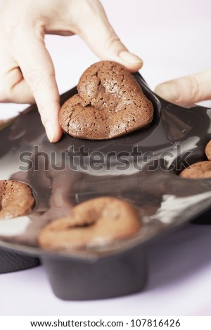 Removing the chocolate hearts from the moulds - stock photo
