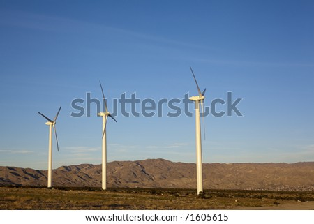 Renewable electricity generating wind mill turbine towers in desert mountain corridor, Palm Springs, CA - stock photo