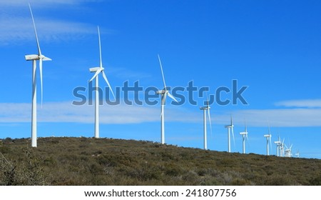 Renewable energy, clean green energy - A row of wind turbines on top of a mountain/hillside with a bright blue sky