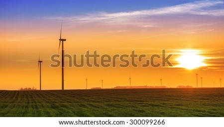 Renewable energy concept, windmills at sunset. - stock photo