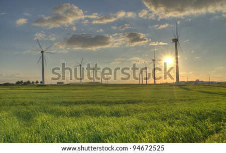 Renewable energy wind turbine in green field sunset images - stock photo