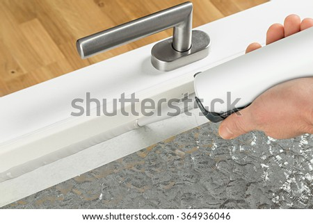 renewing of a silicone joint on a window - stock photo