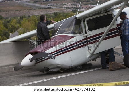 RENO, NEVADA - MAY 24, 2016:  A single engine Cessna aircraft crash lands on a highway after suffering catastrophic engine failure.  No reported injuries.  FAA and NTSB are investigating. - stock photo
