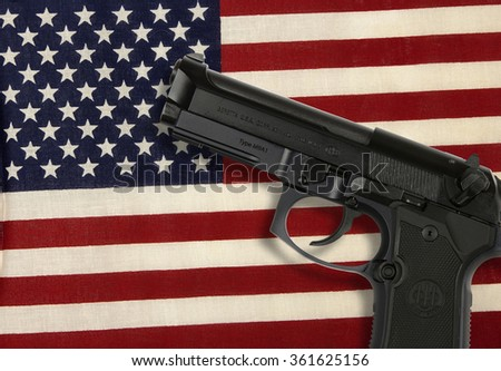 RENO, NEVADA - SEPTEMBER 9, 2016: A 9mm handgun on an American flag representing the right of Americans under the 2nd amendment to the U.S. Constitution to keep and bear arms for personal protection. - stock photo