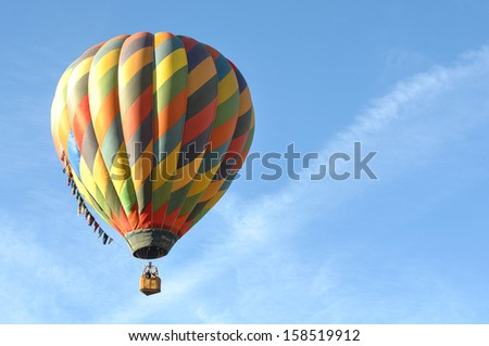 RENO - SEPTEMBER 8: A colorful hot air balloon rises into the clear blue sky during the mass ascension at the 37th annual Great Reno Balloon Race in Reno, Nevada on Sept. 8, 2012