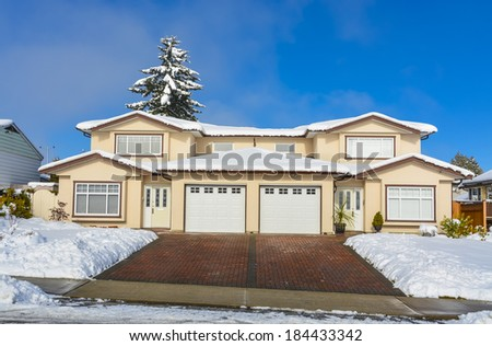 Renovated duplex house on winter season. Block paved driveway to the garages. - stock photo