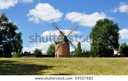 renovated windmill in a field with blue sky and clouds background - stock photo