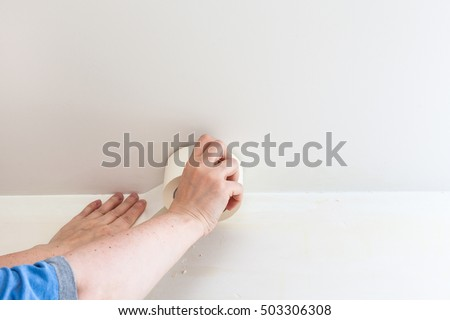 Renovation Of Apartment   Preparation Of Walls For Painting. Painter Fixes  Sticky Tape On Wall