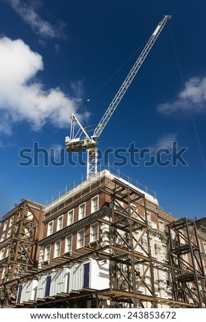 Renovation of red brick building with crane and scaffolding. Material storage containers. - stock photo