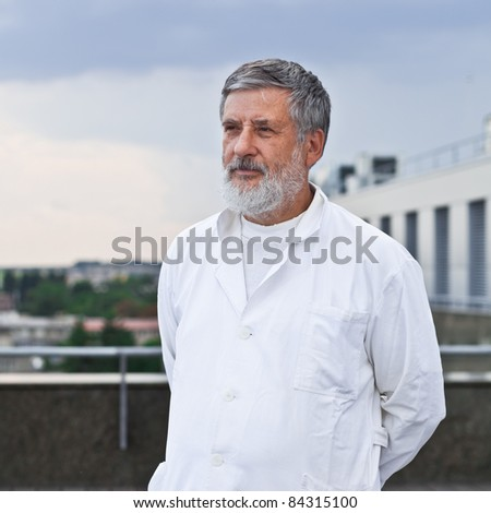 renowned scientist/doctor standing on the roof of the research center/hospital looking confident (color toned image)