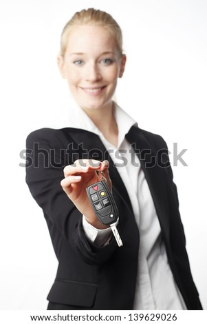 Rent a car! Smiling businesswoman giving car key. Isolated on white (focused on key)  - stock photo
