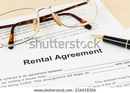 Rental agreement document with glasses and pen, document is mock-up - stock photo