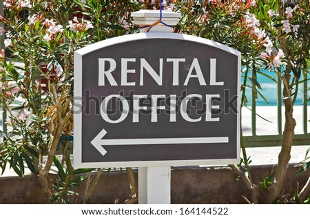 Rental sign shows direction where the office is located at.  - stock photo