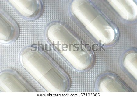 Rep capsules in foil, closeup, isolated with shadow - stock photo