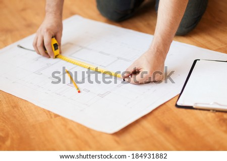 repair, building and home concept - close up of male hands measuring blueprint - stock photo