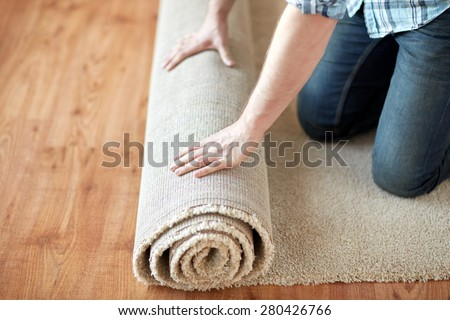 repair, building and home concept - close up of male hands rolling carpet - stock photo
