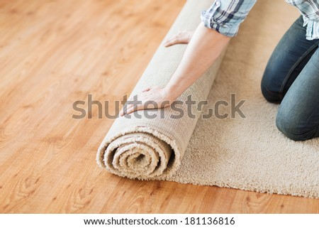 repair, building and home concept - close up of male hands unrolling carpet - stock photo