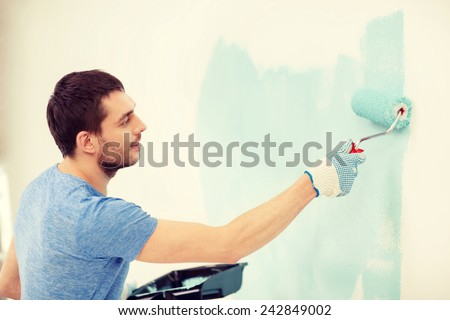 repair, building and home concept - smiling man painting wall at home - stock photo