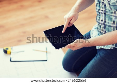 repair, building, technology and home concept - close up of male with tablet pc, blueprint and measuring tape - stock photo