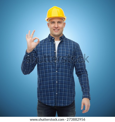 repair, construction, building, people and maintenance concept - smiling male builder or manual worker in helmet showing ok sign over blue background - stock photo
