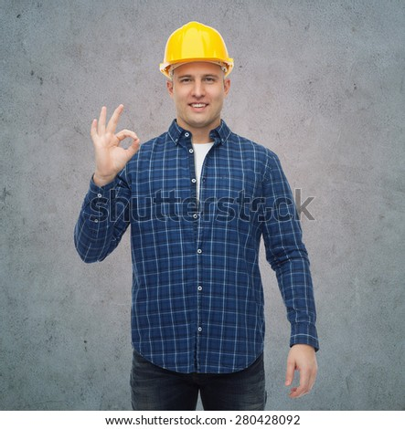 repair, construction, building, people and maintenance concept - smiling male builder or manual worker in helmet showing ok sign over gray concrete wall background - stock photo