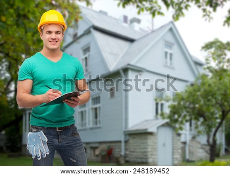 repair, construction, people, building and maintenance concept - smiling male manual worker in protective helmet taking notes to clipboard over house background - stock photo