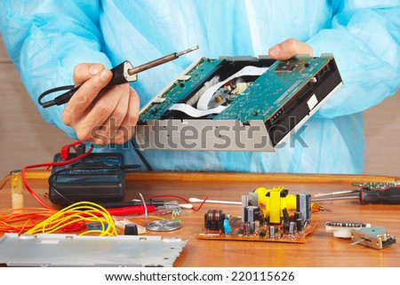 Repair electronic hardware with a soldering iron in the service workshop - stock photo