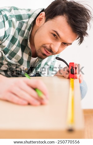 Repair home concept. Close-up of man is measuring wooden board with measuring tape. - stock photo