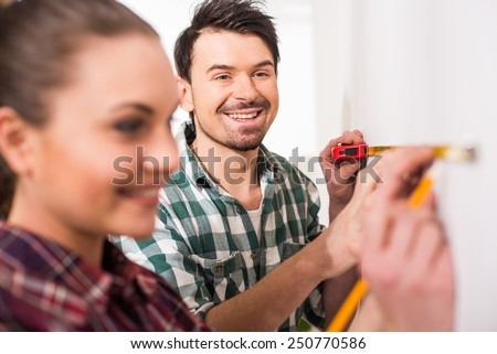 Repair home concept. Young couple are measuring a wall with measuring tape. - stock photo