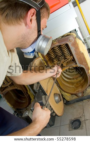 Repair man servicing big gas boiler - stock photo