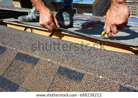 Repair Of A Roofing From Shingles. Roofer Cutting Roofing Felt Or Bitumen  During Waterproofing Works