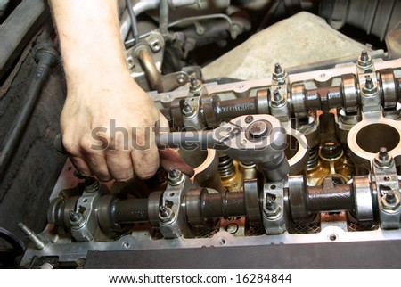 Repair of the engine. A hand with the tool. Automobile service