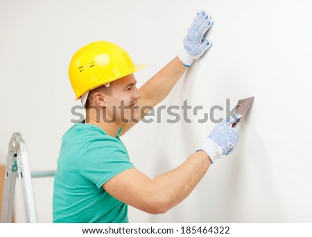 repair, renovation and home concept - smiling man in helmet doing renovations at home - stock photo