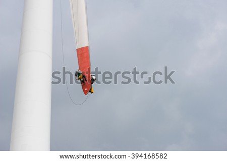 repair work on the blades of a windmill for electric power production - copy space - stock photo