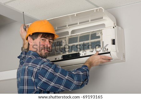 Repairer conducts adjustment of the indoor unit air conditioner. - stock photo