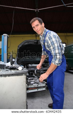 Repairer working on vehicle in garage - stock photo