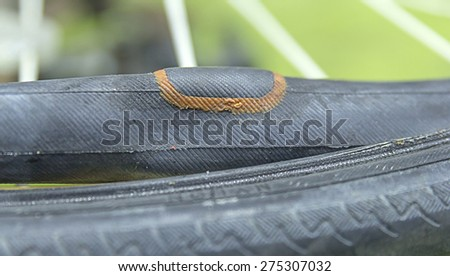 Repairing a flat tire of an bicycle tire. Patched up inner tube of an bicycle tire - stock photo
